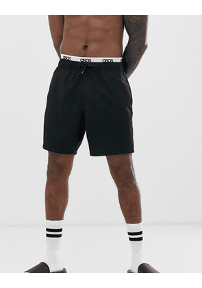 ASOS DESIGN swim short with double layer waistband in black in mid length