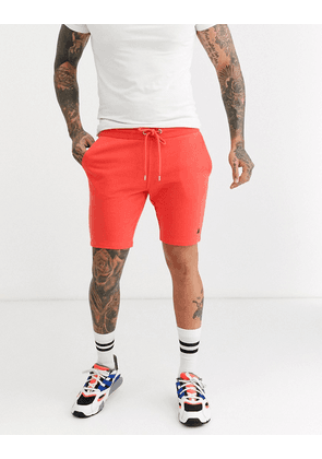 ASOS DESIGN jersey skinny shorts in coral with triangle-Pink
