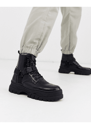 ASOS DESIGN lace up boot in black faux leather with strap detail on chunky sole