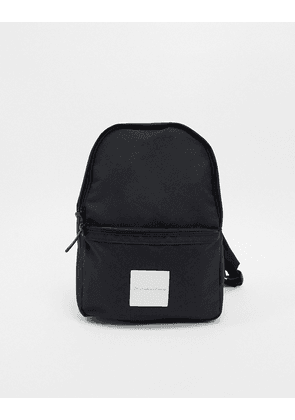 ASOS DESIGN mini backpack in black with white patch and gold unrvlld spply signature
