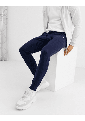 ASOS DESIGN organic skinny joggers in navy with triangle