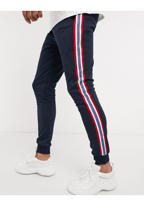 ASOS DESIGN skinny joggers with side stripe taping in navy