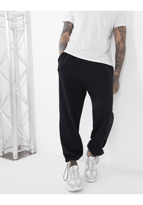 ASOS DESIGN oversized joggers in black with toggle hem