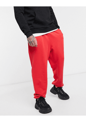 ASOS DESIGN oversized joggers in red with toggle hem