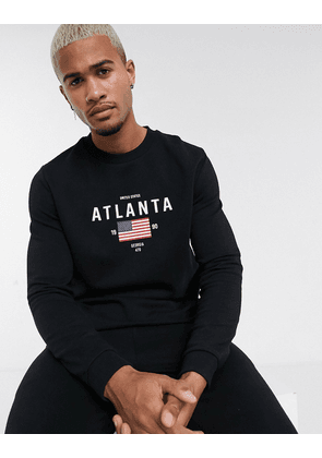 ASOS DESIGN tracksuit in black with city flag chest print