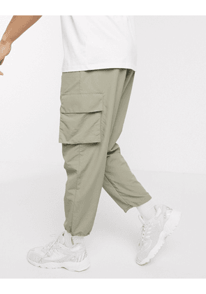 ASOS DESIGN tapered nylon cargo joggers with toggle hem-Green