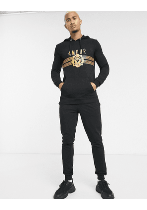 ASOS DESIGN tracksuit with hoodie and skinny jogger with amour print-Black