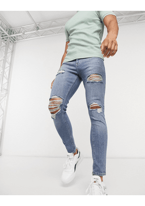 ASOS DESIGN spray on 'vintage look' jeans with power stretch in mid blue with heavy rips