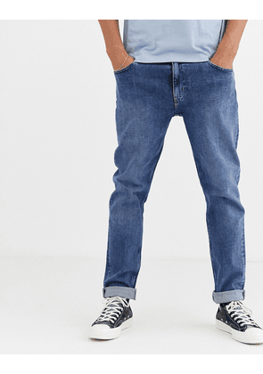 ASOS DESIGN stretch tapered jeans in flat mid wash blue