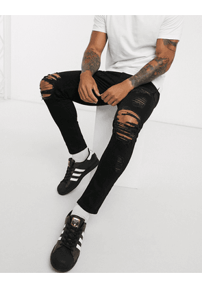 ASOS DESIGN cropped skinny jeans in black with heavy rips