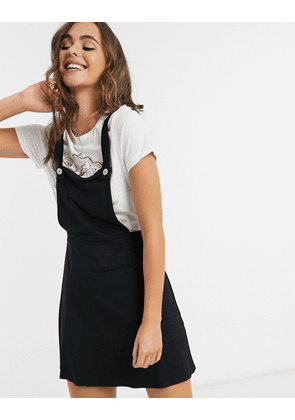 ASOS DESIGN mini pinafore skirt with buttons in black