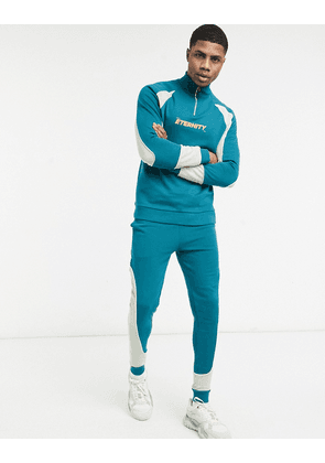 ASOS DESIGN tracksuit with half zip in colour block panels & chest print-Green