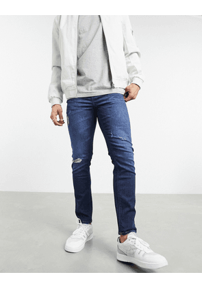 ASOS DESIGN cropped skinny jeans with 'less thirsty' wash in dark blue with rips