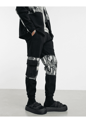 ASOS DESIGN co-ord polar fleece tapered joggers with abstract camo panels & utility pockets in black