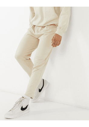 ASOS DESIGN organic tapered joggers with pleats in beige-Neutral