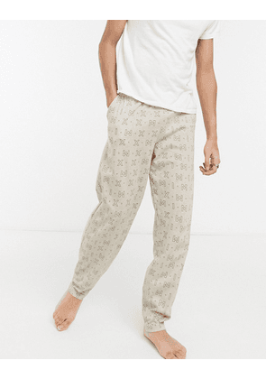 ASOS DESIGN lounge trousers with roman numeral print-Beige