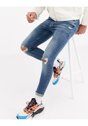 ASOS DESIGN spray on jeans in power stretch with rips in vintage greencast-Blue