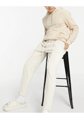 ASOS DESIGN smart pique tapered joggers with fixed hem & pin tucks in beige-Neutral