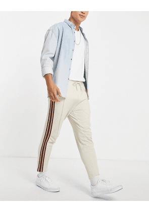 ASOS DESIGN tapered fixed hem joggers with pin tucks & side tape in beige-Neutral