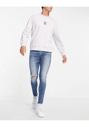ASOS DESIGN spray on jeans with powerstretch in mid wash blue with knee rip