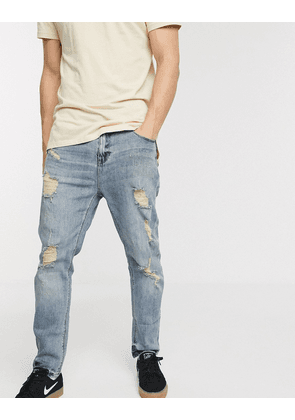 ASOS DESIGN relaxed tapered jeans in light wash blue with heavy rips