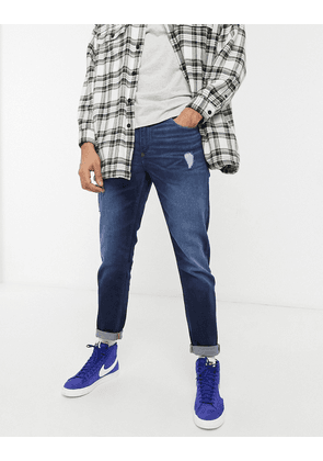 ASOS DESIGN tapered jeans with 'less thirsty' wash in dark blue with abrasions